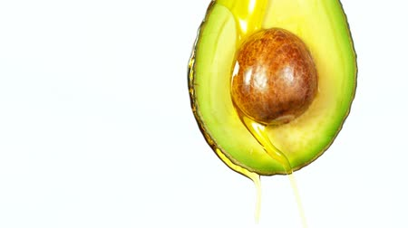 sementes : Fresh cut avocado with oil stream. Concept of healthy fruit also useful in cosmetics. Stock Footage