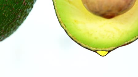 vitamina : Fresh cut avocado with oil stream. Concept of healthy fruit also useful in cosmetics. Stock Footage