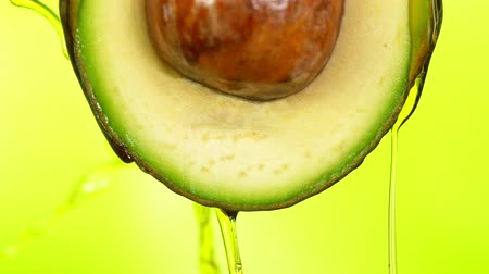 bezuinigingen : Fresh cut avocado with oil stream. Concept of healthy fruit also useful in cosmetics. Stockvideo
