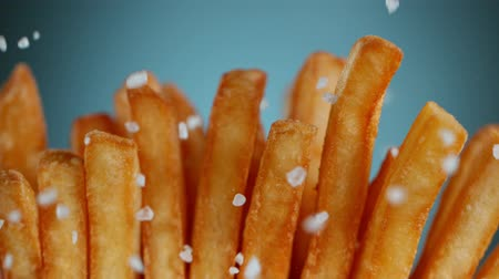 batatas : Super Slow Motion Detail Shot of adding Salt on Fresh French Fries