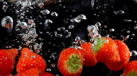 vibráló : Exploding strawberries with water on a black background.