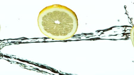 Fresh Lemon Slices Falling with Water Splash Cascade in Super Slow Motion