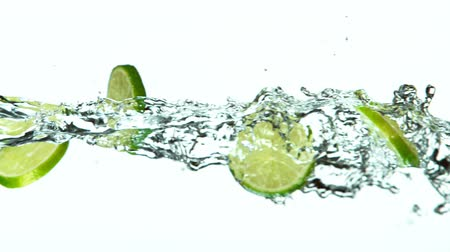 Fresh Lime Slices Falling with Water Splash Cascade in Super Slow Motion