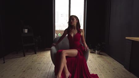 dama : A gorgeous red-haired lady in an elegant red dress is sitting in a chair. Wideo