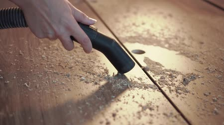 Close-up - cleaning with a building vacuum cleaner. Removal of sawdust