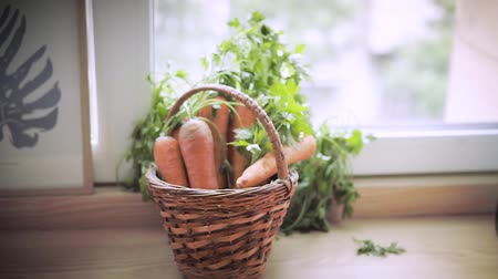 антиоксидант : A wicker basket with a young carrot stands on the window