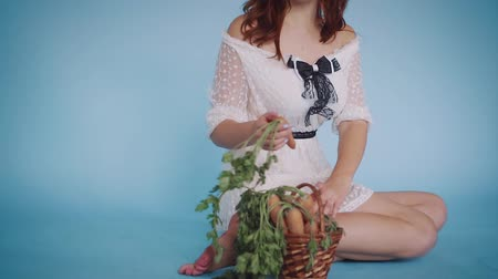 Girl-bunny sits on the floor and takes out a basket of carrots. Dostupné videozáznamy