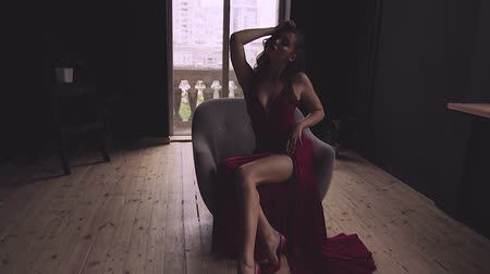 A gorgeous red-haired lady in an elegant red dress is sitting in a chair. Dostupné videozáznamy
