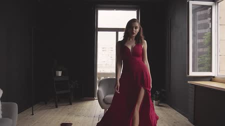 A gorgeous red-haired lady in an elegant red dress