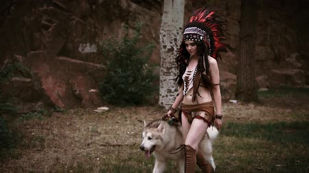 A beauty girl is a Native American walks with a wild wolf. Alaskan Malamute