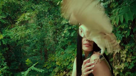королева : A forest nymph with long dark hair walks with a white owl. A girl in an unusual green dress with a deep neckline and bare legs. Background wild nature