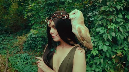 rainha : A forest nymph with long dark hair walks with a white owl. A girl in green dress with a deep neckline and bare legs.