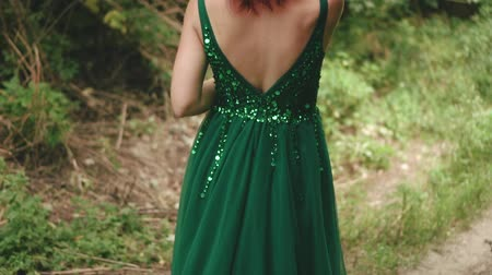 ninfa : Red-haired, curly girl in a green, emerald dress with an open back with a long train. background wildlife. Shooting from the back without a face. Elegant hairstyle with unusual hairpins. art colors