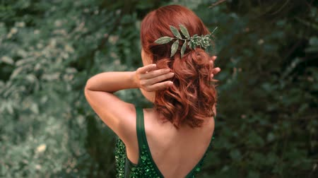 ninfa : A girl in about the image of a forest nymph in a frank, sexy, emerald dress. Shooting from the back without a face, a demo of beautiful styling with green ornaments in the hairdo