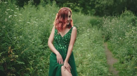 ninfa : Girl with red curly hair in a green emerald dress in a wild forest posing on the camera. smiles and gently strokes his bare leg. background nature. creative colors.