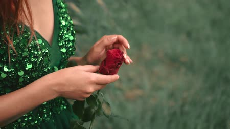 ninfa : A girl without a face with red curly hair in a green emerald dress in the forest. holding a scarlet rose in her hands. background wildlife. creative colors.