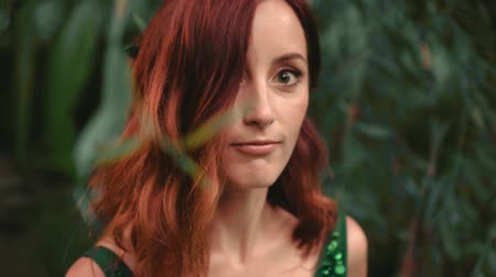 ninfa : A girl with red curly hair in a green emerald dress in the forest. funny and cheerfully croaks at the camera, scares and smiles. background wildlife. creative colors. Vídeos