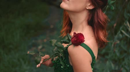 yay : Portrait of a red-haired girl, close-up. The backwater woman with her eyes closed, holds a scarlet rose in her hands. Luxurious evening dress, emerald dress with open back
