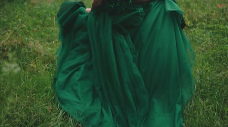 mese : Red-haired girl in a luxurious green dress with sparkling beads. The princess runs through a forest glade, a long train waving in the wind. Shooting from the back without a face. Slow motion. Stock mozgókép