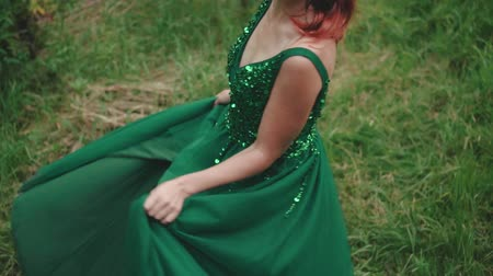 ninfa : Red-haired girl in the image of a forest nymph, spinning in a luxurious, long, green dress, which is embroidered with sparkling beads. Shooting without a face. Slow motion