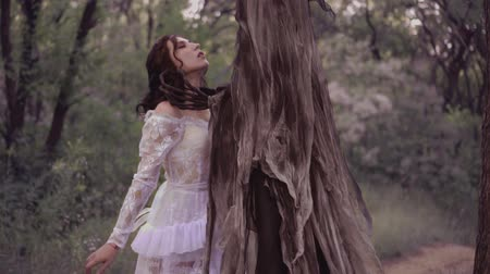 grim : The good fairy closes her eyes in front of evil, preparing for death. princess in the clutches of a terrible monster and killer. forest nymph in white dress against the spirit of darkness Stock Footage