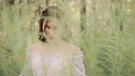 ninfa : medieval lady with dark wavy hair in a white luxurious light vintage summer dress with a mesh and floral patterns walks slowly in an amazing forest alone, pushing the grass in her way, turning round