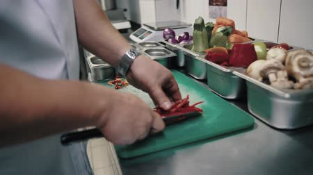 pimentas : chef cuts bell pepper and puts in a white container