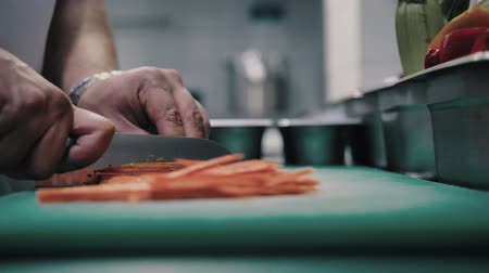 pimentas : chef cuts carrot with a sharp knife