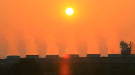 building heat : foggy smoke from heavy industry chimney against beautiful sun light behind Stock Footage