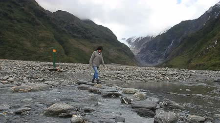 woman tourist walking in franz josef glacier trail most popular traveling destination in south island new zealand Стоковые видеозаписи