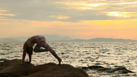 woman playing yoga at sea side against sun rising sky