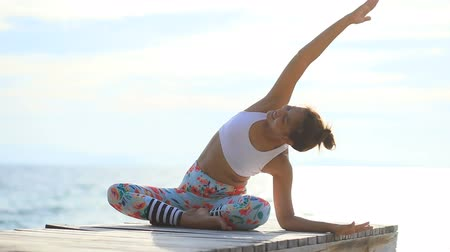 asian woman playing yoga on beach pier