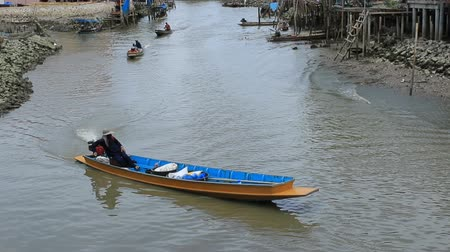 villager in klong kon samuthsakorn thailand sailing long tail boat in canal
