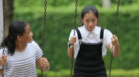 asian teenager playing on swing at playground