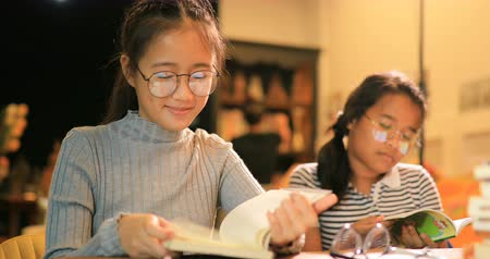 умный : asian teenager reading book in school library
