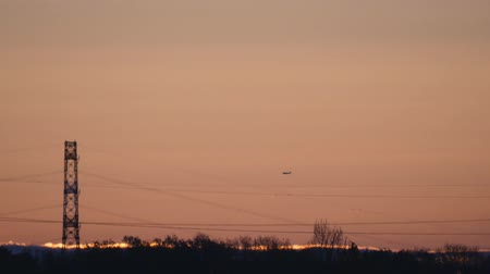 traverse : An aircraft approaches an airport toward north just before the sunrise.