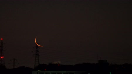 félhold : Tokyo, Japan-February 14, 2018: (Time lapse) A very slim moon is rising beyond power lines. An aircraft for Hanaeda airport passes.