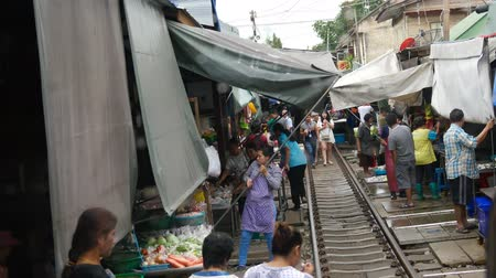 maeklong : Samut Songkhram, Thailand-October 16, 2016: Double speed view of Mae Klong railway market from the Mae Klong line train cab in Stock Footage