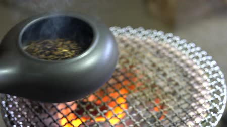 dřevěné uhlí : Chiba, Japan-February 19, 2019: Roasting green tea with an earthenware baking pan on Earthen charcoal brazier. Roasted green tea is called Hojicha in Japanese.