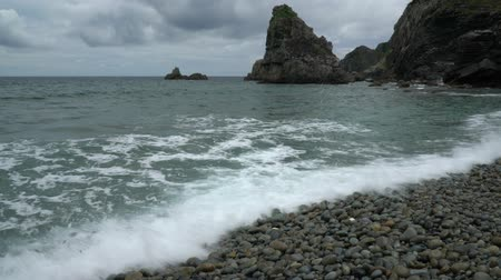 amami : Amami Oshima, Japan - June 18, 2019: Honohoshi beach in Amami Oshima famous for rattles of stones on the beach Stock Footage