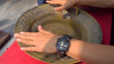 esfregar : Udon Thani,Thailand-January 24, 2020: Demonstration of China Spouting Bowl or Tibetian Dancing Water Bowl or Resonating water bowl. Due to the vibrations caused by the rubbing of the handles, the water surface begins to ripple around the rim.