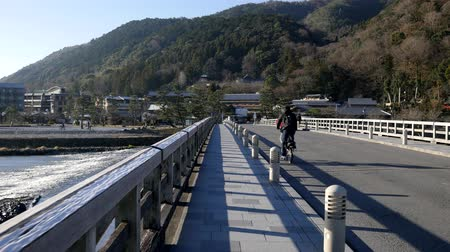 Kyoto,Japan-February 24, 2020: Crossing Togetsu-kyo Bridge in Arashiyama, Kyoto