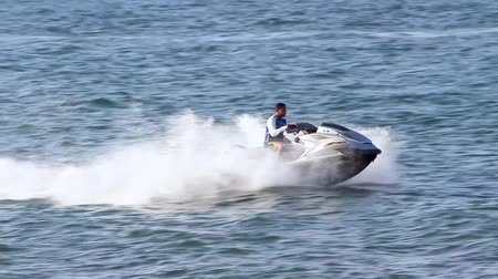 глубоко : Ocean scene people boating and entertaining water travel through ships boats ocean, motors and vehicles drafting on sea water, people doing jet ski on deep water high tides rising on Oman beach
