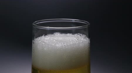 alkol : Beer Pouring into a Glass Against a Black Background