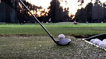 тройник : Hitting a Golf Ball with a Driver Golf Club at a Driving Range in the Early Evening Стоковые видеозаписи