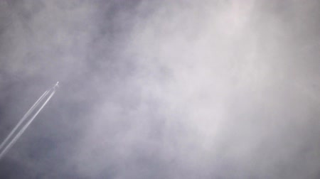мониторинг : Footage, using a telephoto lens of an airplane flying high in the clouds.