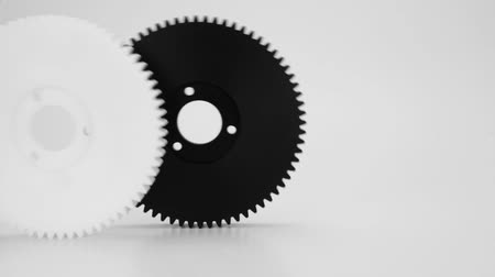 kaseta : Rolling plastic gears in black and white, isolated on a white background.