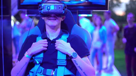 A young blonde man sitting testing the helmet of virtual reality