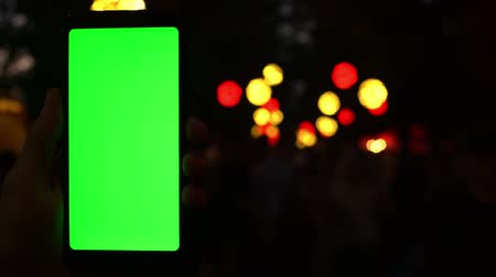 Man using cell phone chinatown holding greenscreen chromakey at evening bokeh blurred lights lighting unfocused background, commerce concert concept and online tickets buy 4k