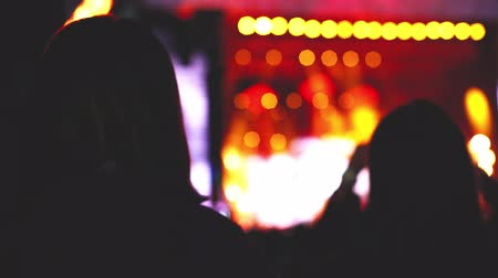 Portrait of dancing girl on the concert, background of silhouettes of people at a concert with a flashing light 4k